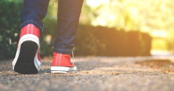 Close up of a person's lower legs and feet, walking with red sneakers outdoors.