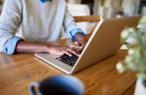 Closeup of an African American female entrepreneur working online with a laptop while sitting at her table at home